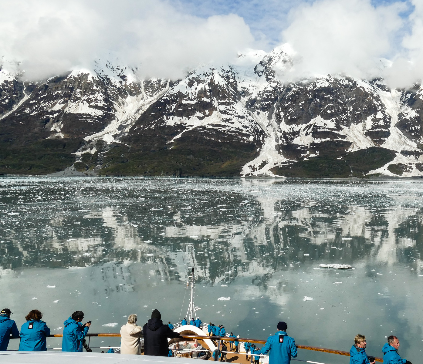 Passengers on a Hubbard Glacier cruise watch mountains reflected into Disenchantment Bay.