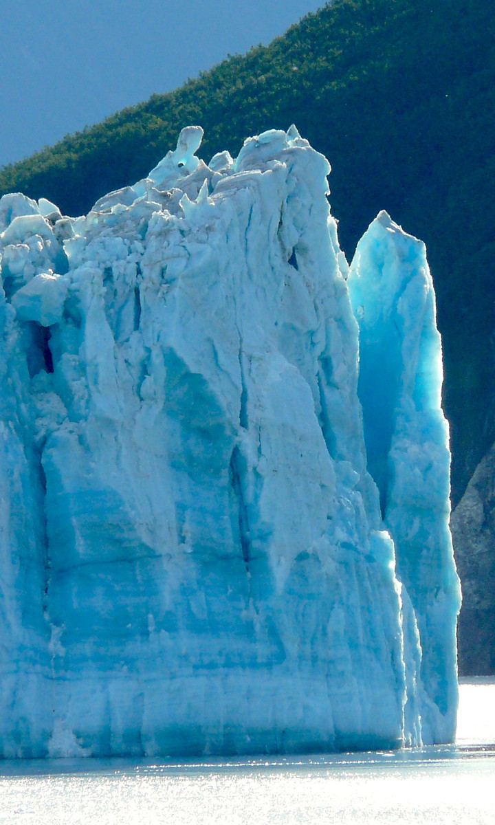Jagged edge of Hubbard Glacier with light turning the ice to blue.