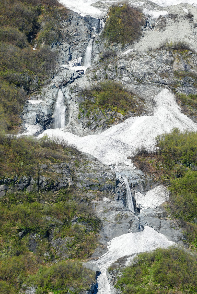 Water falls flow down the mountainside from melting snow.