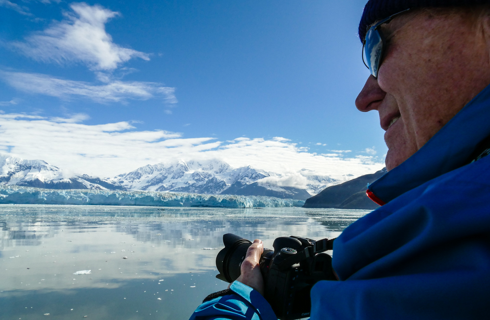 Man on a ship photographing a glacier.