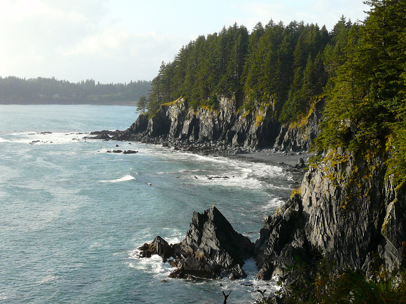 Hiking Kodiak Island leads to this rocky view of cliffs, evergreen trees and the ocean.