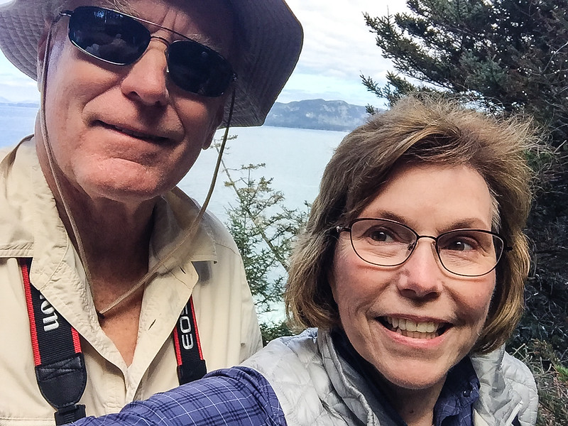 A boomer couple poses wearing Alaska cruise attire for a hike on Kodiak Island, with the ocean in the background.