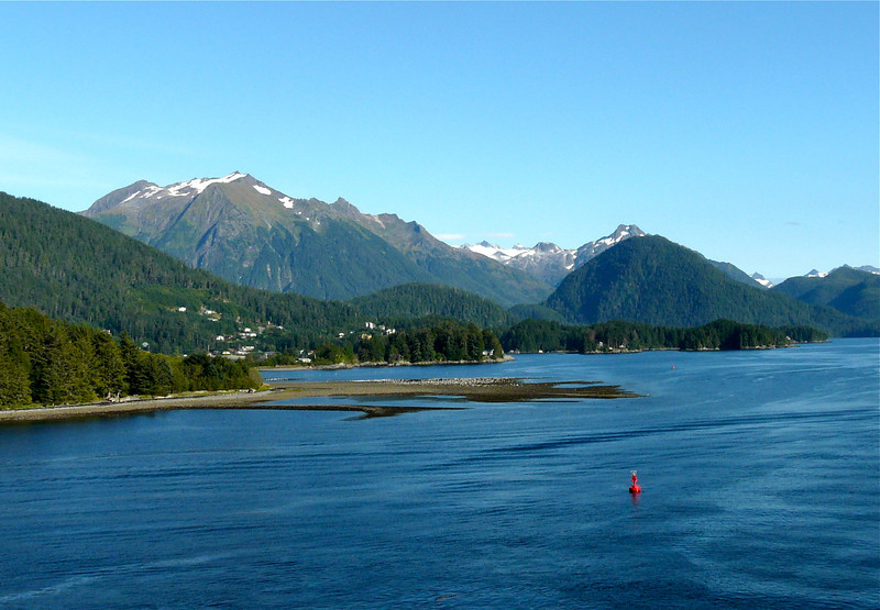 The blue waters of Sitka Sound surrounded by the mountains of Tongass National Forest in Alaska.