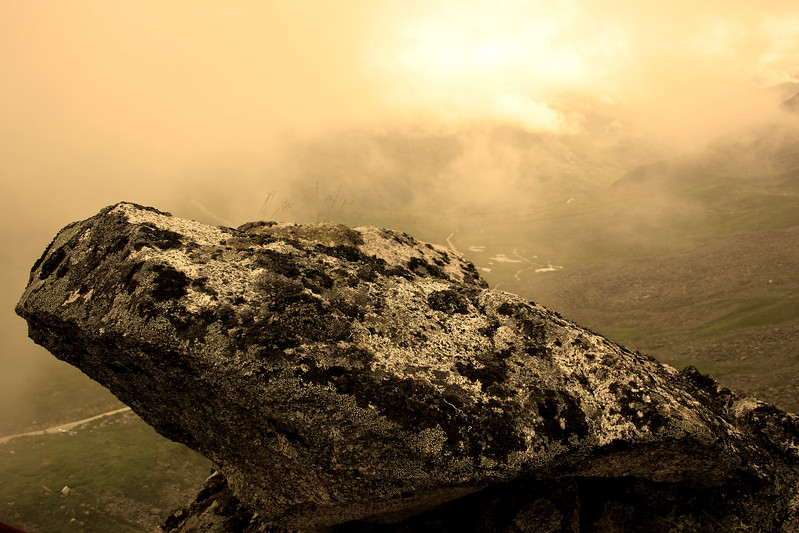 A boulder perched on the top of the climb, with a little sepia effect.
