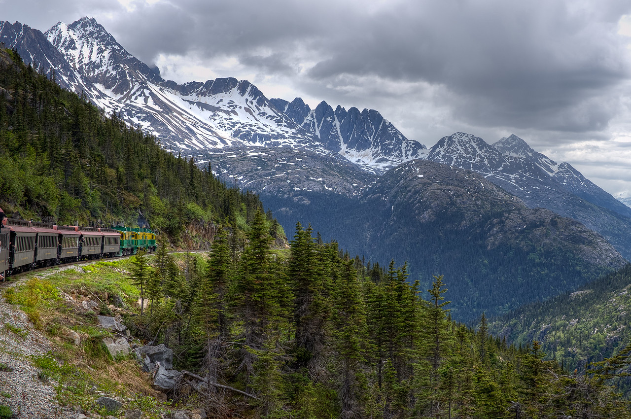 The White Pass Train navigates a cliff along the route in Alaska