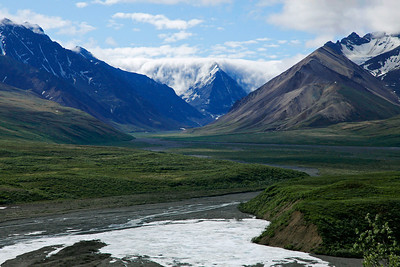 Denali, Alaska In Denali National Park and Preserve, low hanging clouds pour over the mountains in the distance, while in the foreground glacial runoff forms streams in the wide river bed.