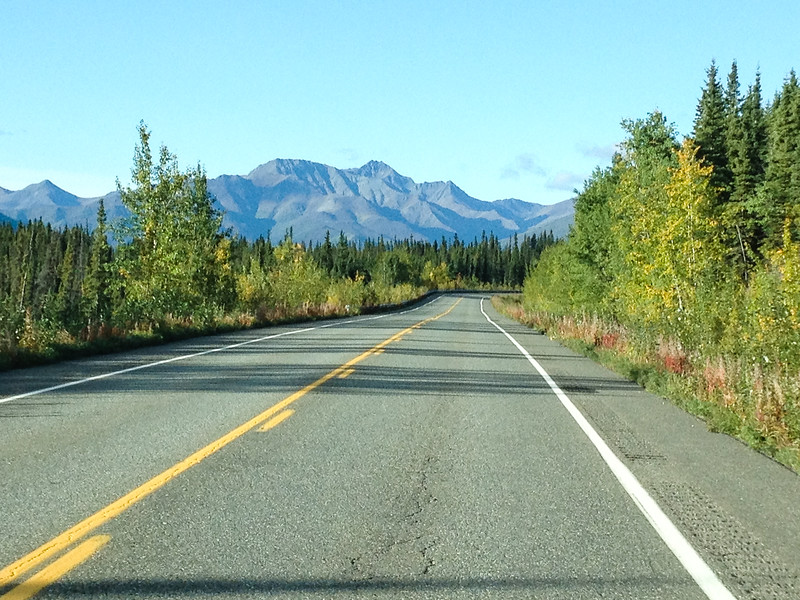 A highway stretches towards the mountains in Alaska. Find out how to get there in our USA road trip planner.