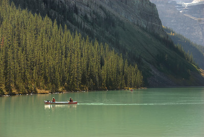 Solitary boat cruising Moraine Lake in the Canadian Rockies of Alberta