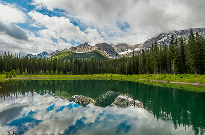 Small pond in Kananaskis Country with a view of the Canadian Rockies - Alberta, Canada
