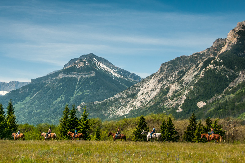 Snow capped mountains and horseback riders - Alberta, Canada