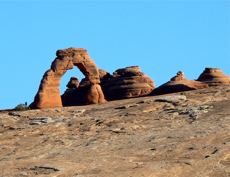In Arches National Park, Delicate arch rises above the sandstone backed by a bright blue sky.