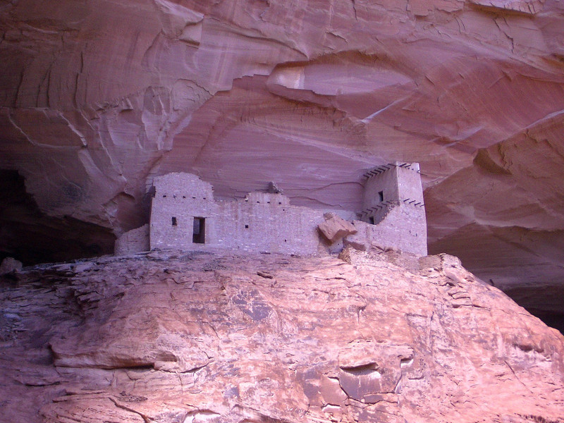 Pink Anasazi ruins tucked into Mummy's Cave in Canyon de Chelly National Monument, one of our recommendations of off-the-beaten-path national parks and monuments.