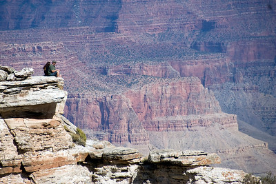 Tourists sitting on a rock cliff at Grand Canyon National Park in Arizona, USA