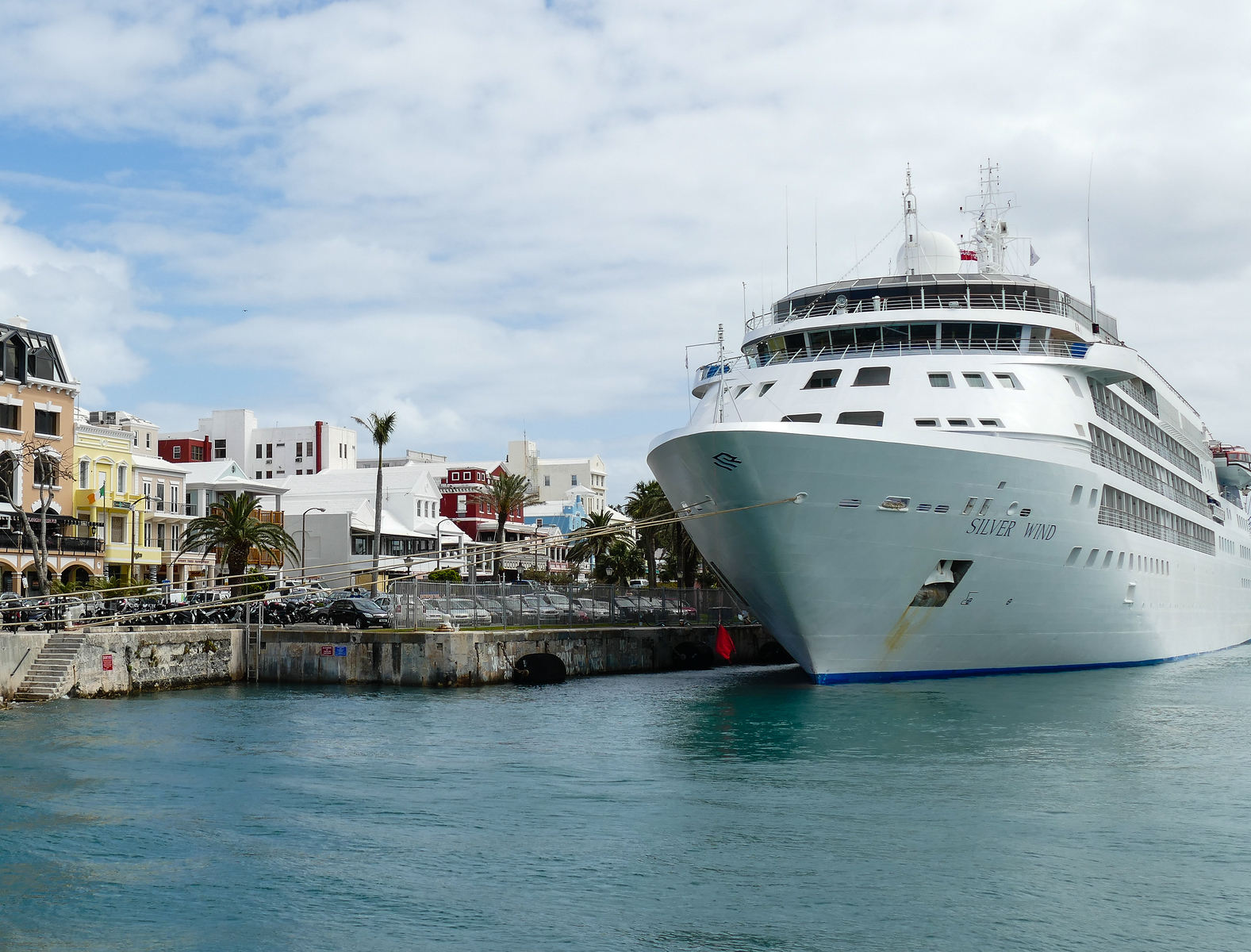 Cruise ship at a dock with colonial buildings lining the sidewalk in Bermuda.