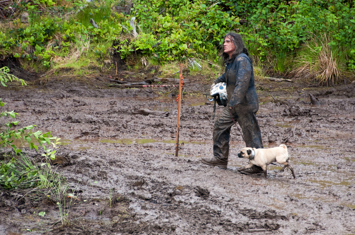 Man walking his dog in the mud, Port Clements, British Columbia