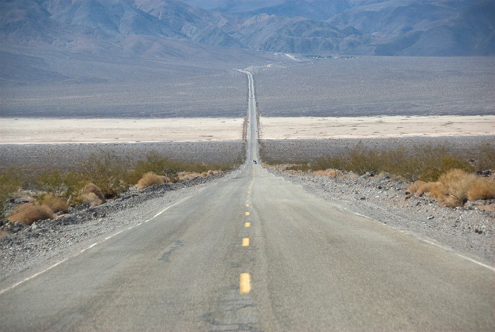 The straight and narrow road is very dry. Death Valley, California