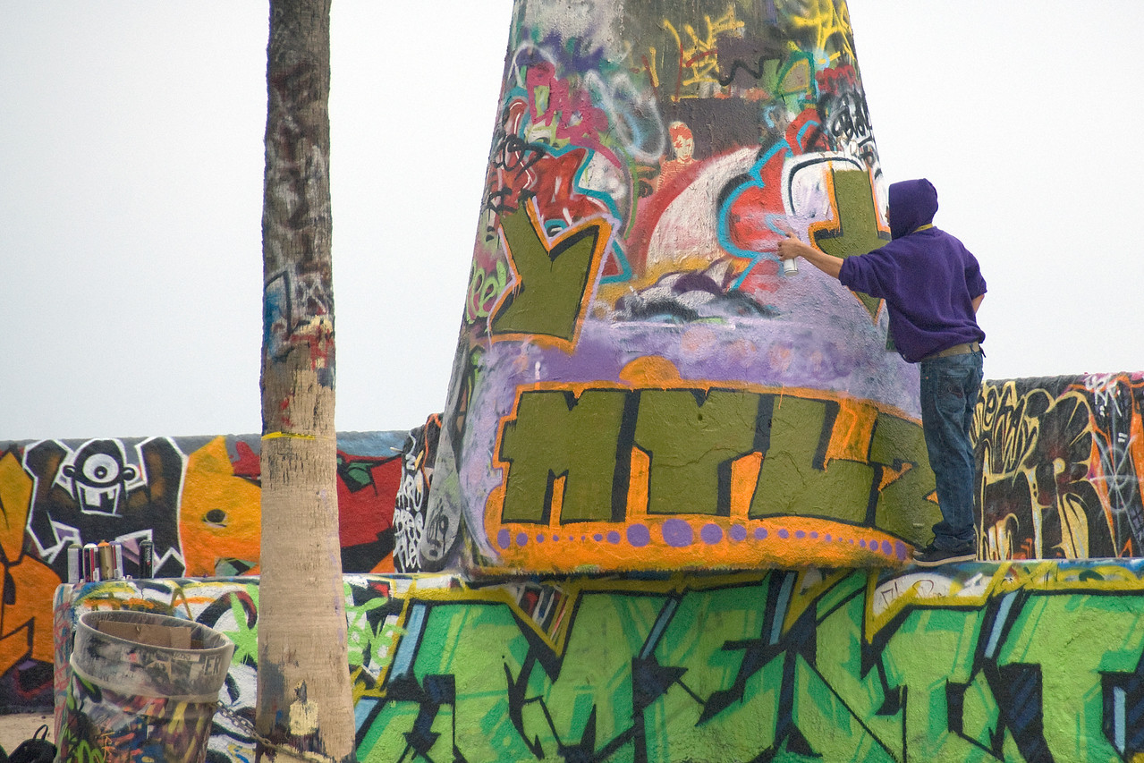 Man spraying graffiti on a wall in Venice Beach, California