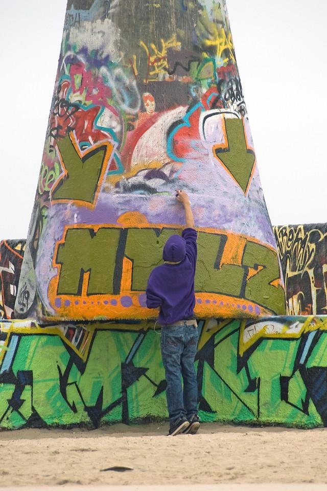 Man spray painting on a wall in Venice Beach, California