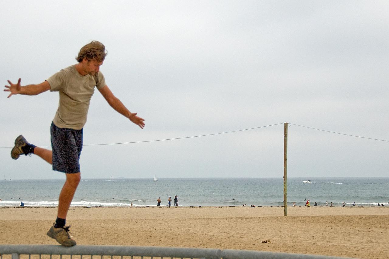 Man balancing on top of a railing in Venice Beach, California