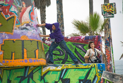 Man spraying on graffiti on a wall in Venice Beach, California