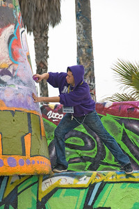 Man spraying graffiti on a wall in Venice Beach, California