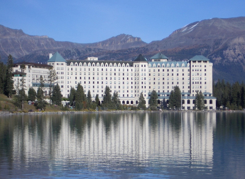 Large hotel reflected into the water at Lake Louise.