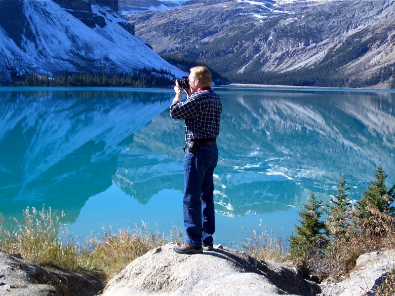 Man standing on a rock taking a photo of mountains reflected in blue water at Bow Lake.