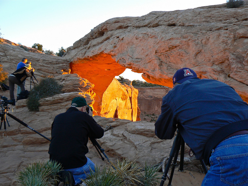 Men bend over tripods capturing the sunrise at Mesa Arch in Canyonlands National Park.