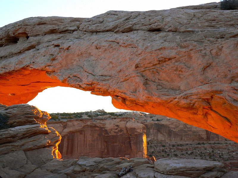 The sunrise glows orange on the underside of Mesa Arch.