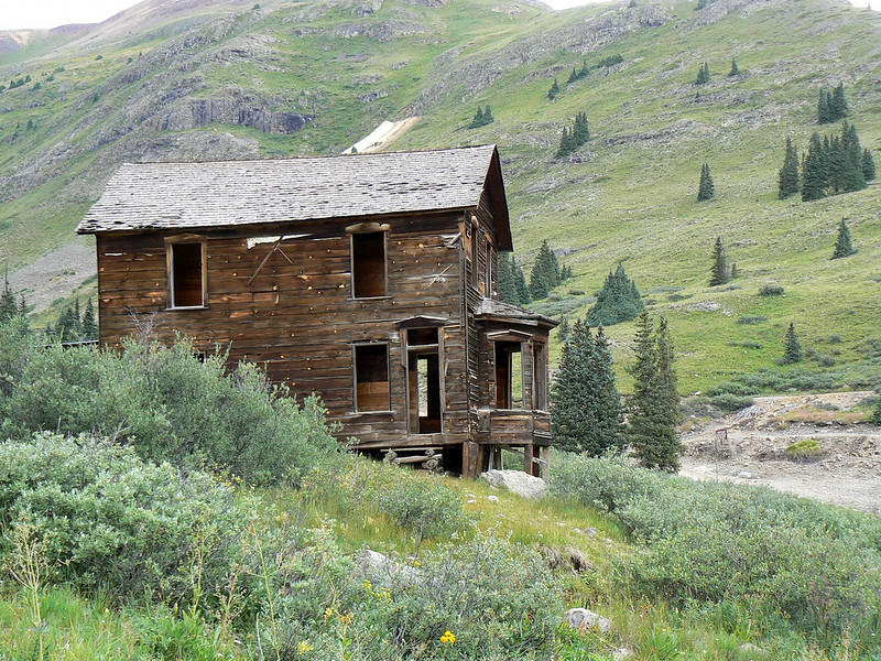 An abandoned building sits between mountains in Colorado.