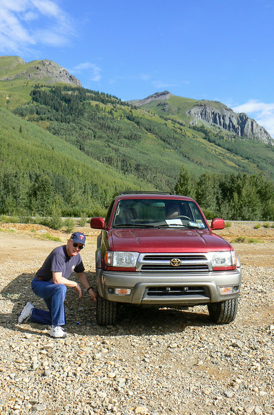 Man kneels by a car tire, letting some of the air out for a driving adventure on the Alpine Loop trail.