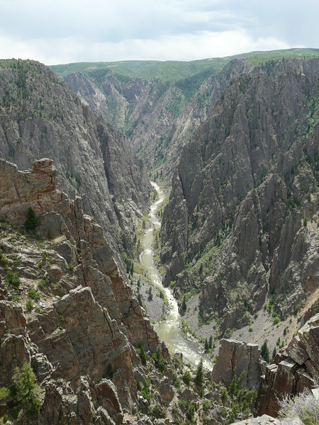 A river winds through the deep chasm at Black Canyon of the Gunnison National Park.