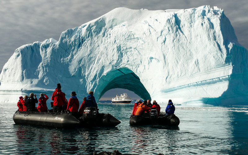Two zodiacs filled with cruise guests photograph an iceberg.