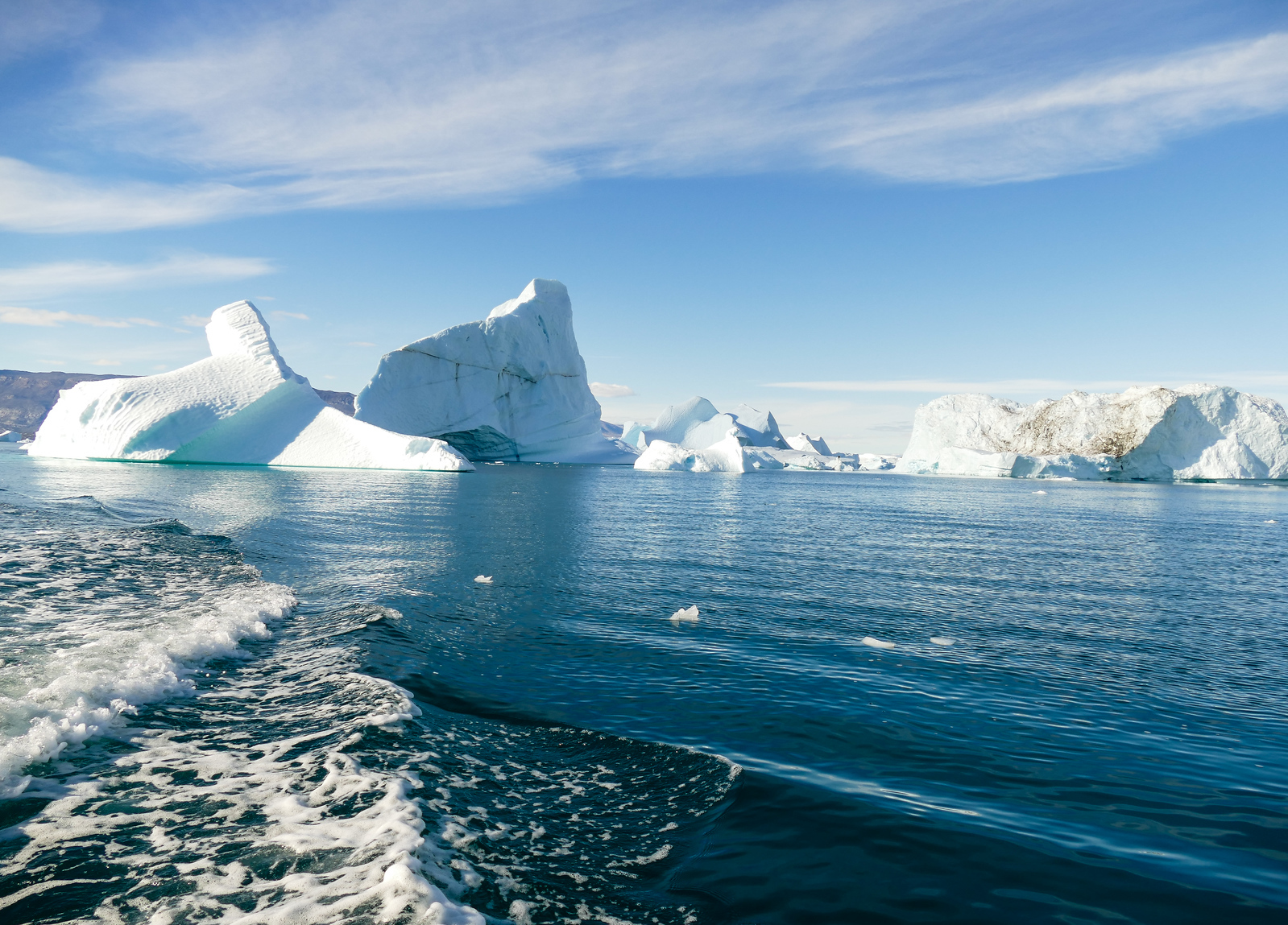 Icebergs scattered around a blue bay at Red Island in Greenland