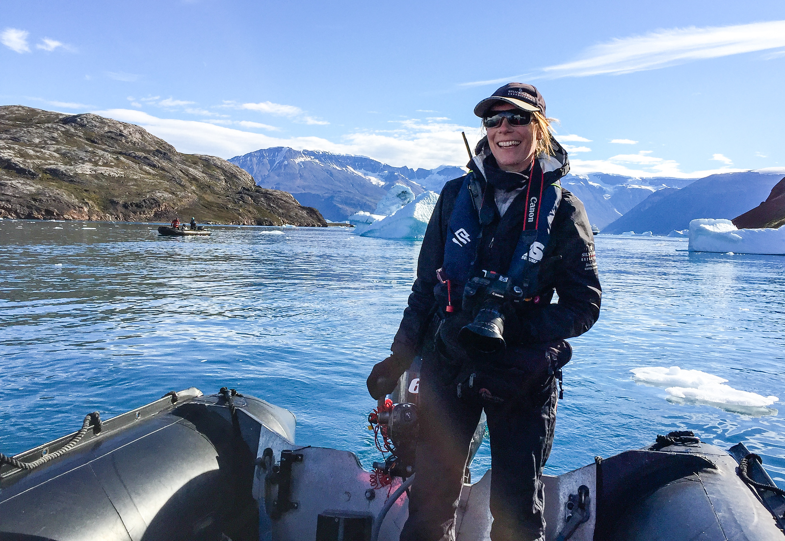 Woman guide stands in a zodiac on an expedition ship excursion