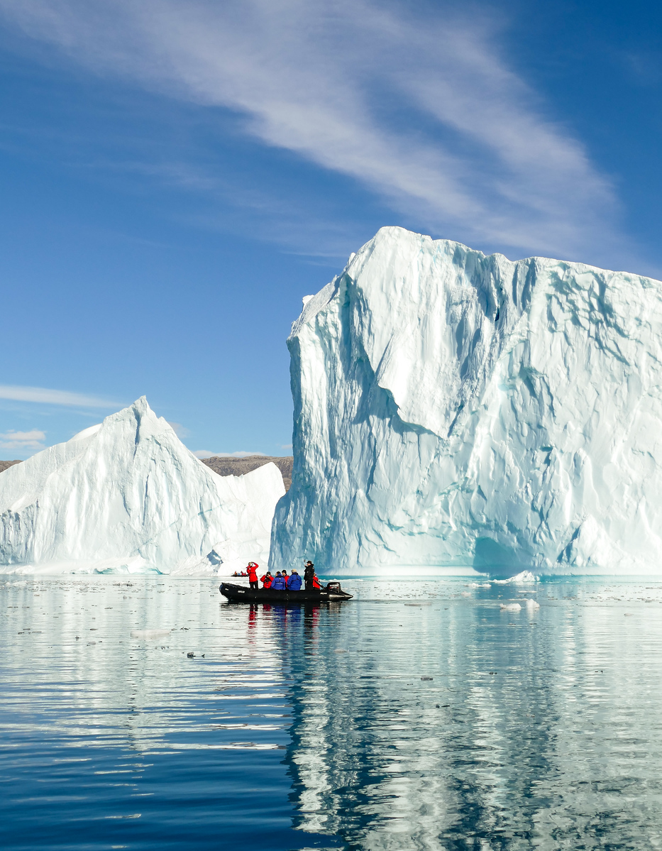 An iceberg dwarfs a zodiac filled with cruise guests near Red Island, Greenland.