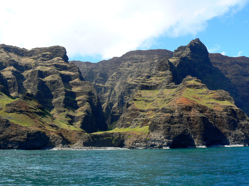An indentation in the green Na Pali Cliffs as seen from the ocean.