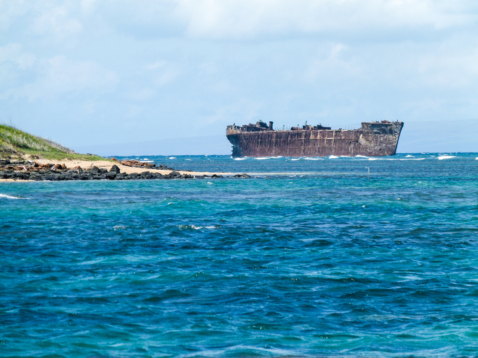 A shipwreck rests in the blue Pacific Ocean off the coast of Lanai.