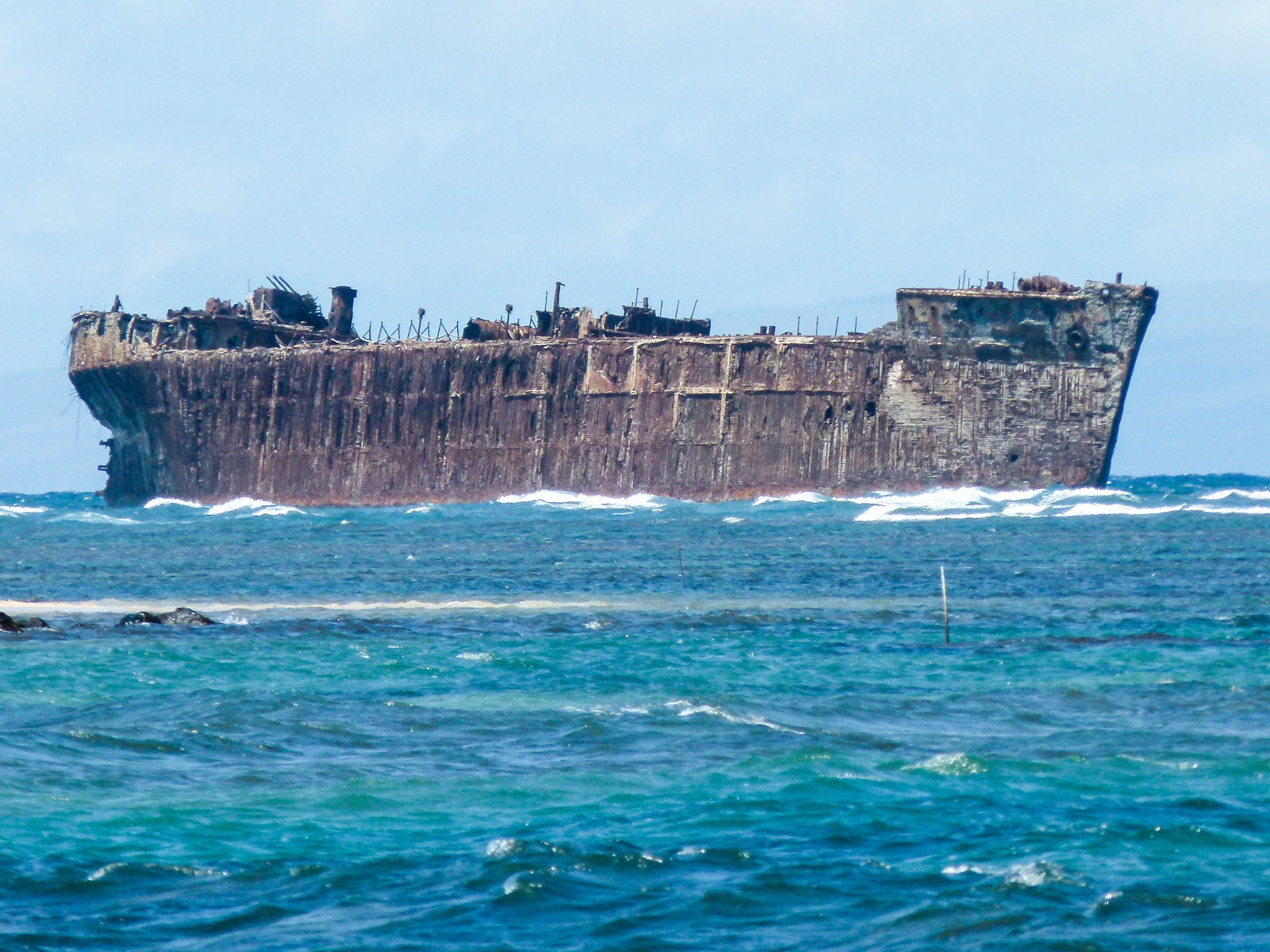 A shipwreck in the blue ocean off the coast of Lanai.