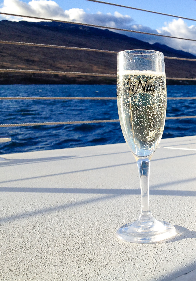 A Maui sunset cruise begins with a glass of champagne. Don't miss this Maui travel experience.