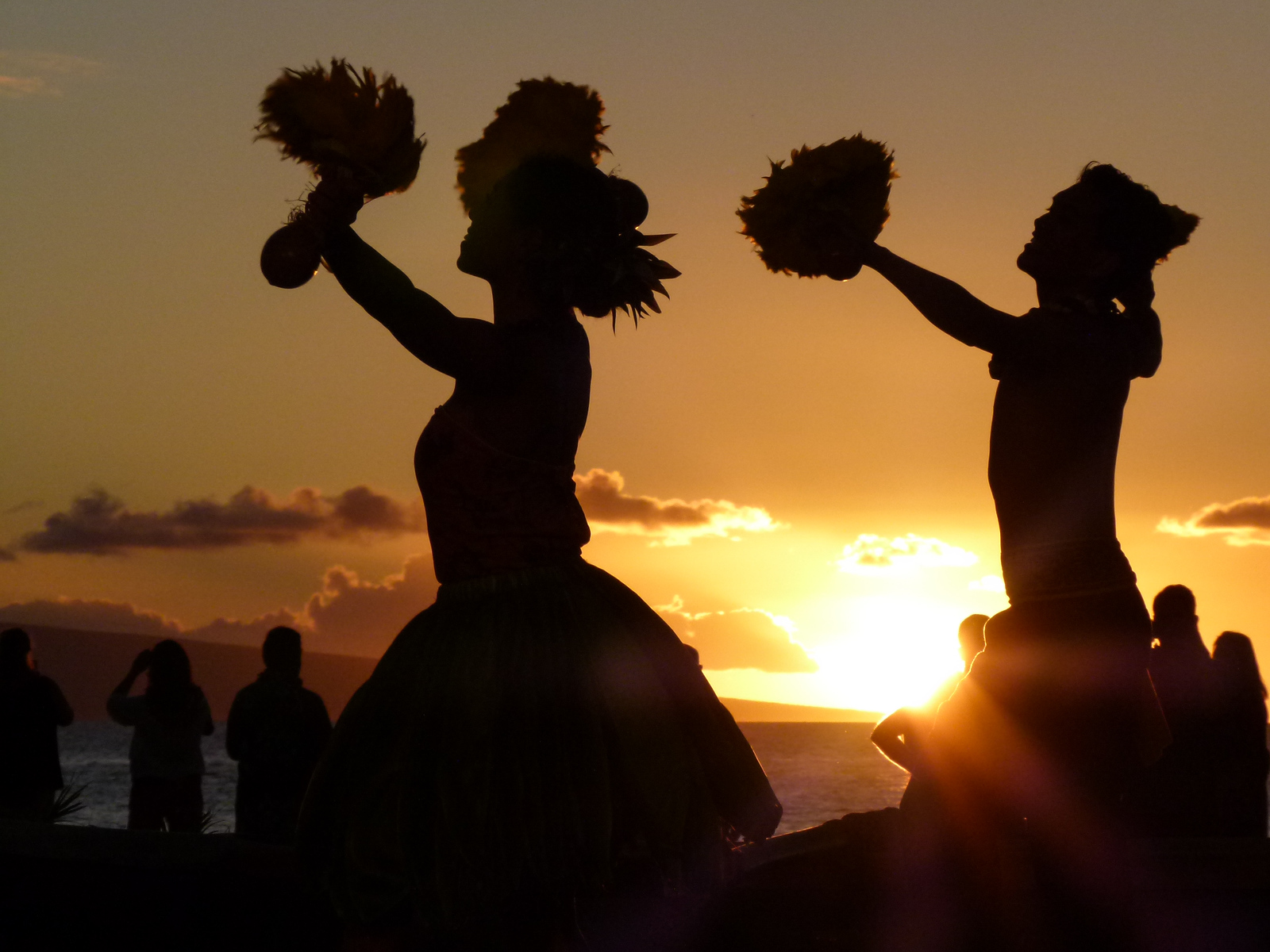 Silhouettes of two hula dancers on Maui as the sun sets.