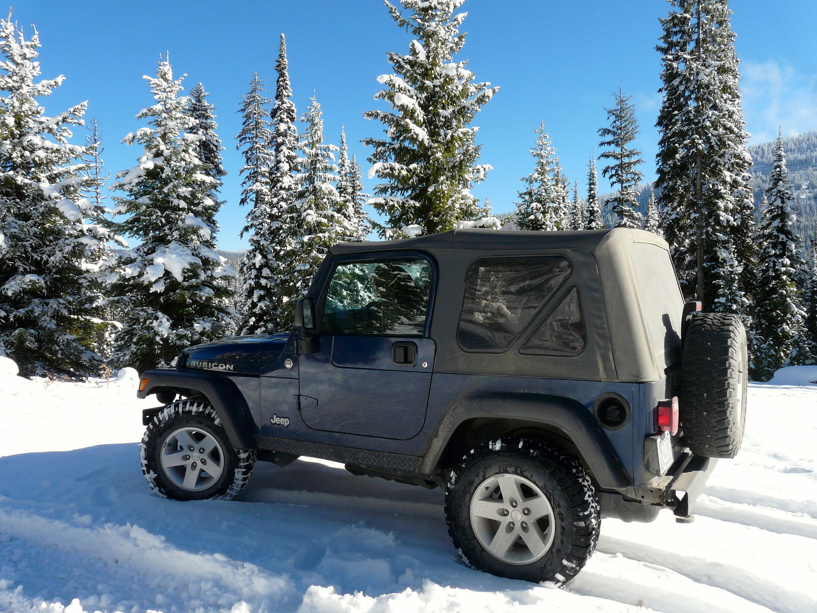 A jeep sits on a road in the snow surrounded by evergreens.