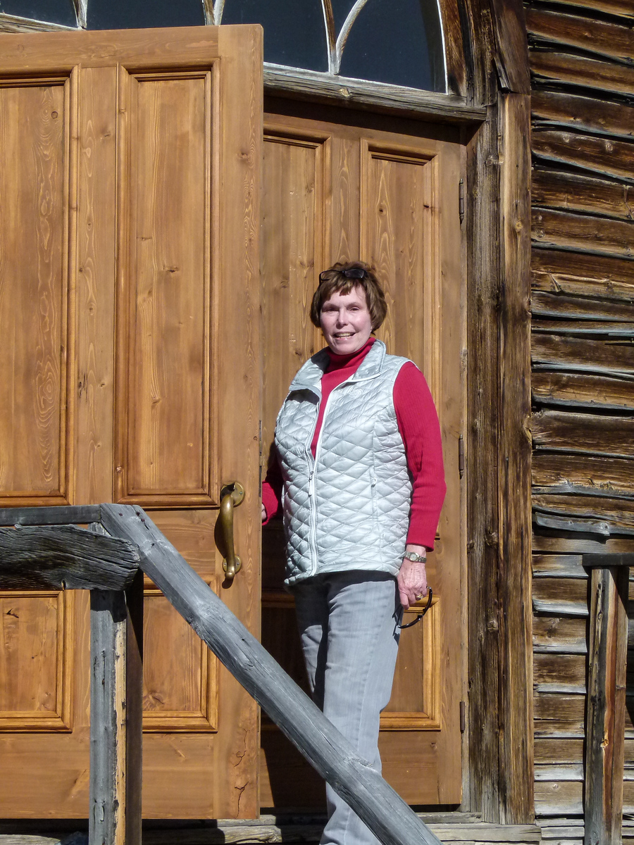 woman opens the door to a log church in a Montana ghost town