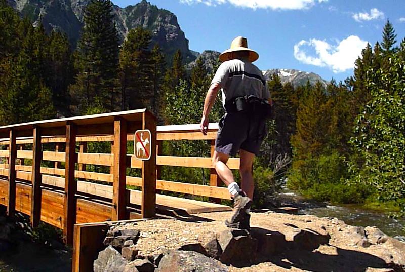Boomer hiker crosses a bridge while hiking the Mystic Lake Trail