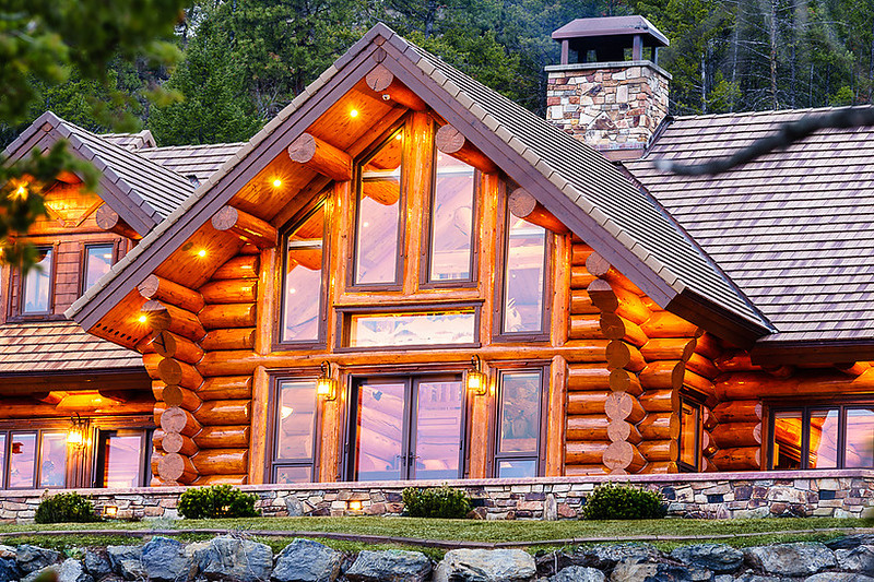 Luxury log house with windows sitting on a hill.