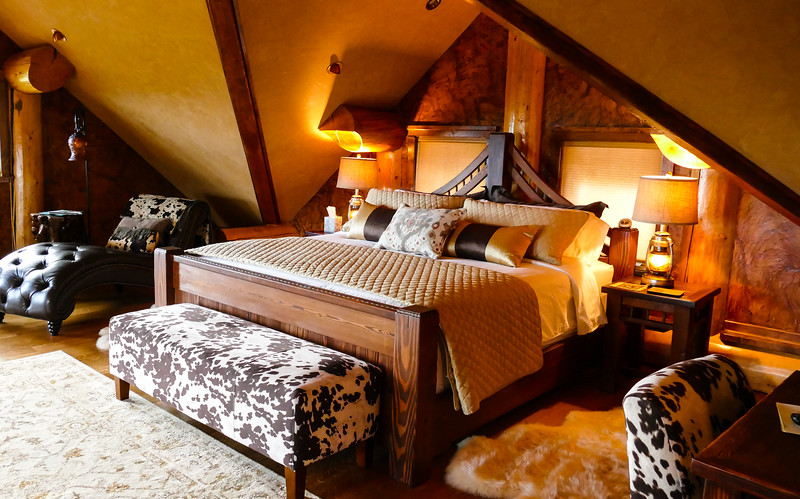 A king size bed with luxurious beige and brown linens has a bench covered in animal print at the end of the bed.