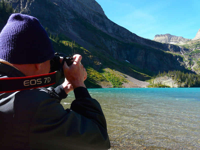 A photographer takes a photo of Grinnell Lake in Glacier National Park.