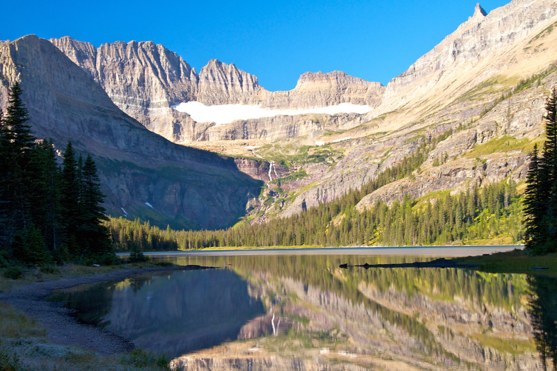 A glaciated mountainside reflects into Swiftcurrent Lake at Many Glacier.