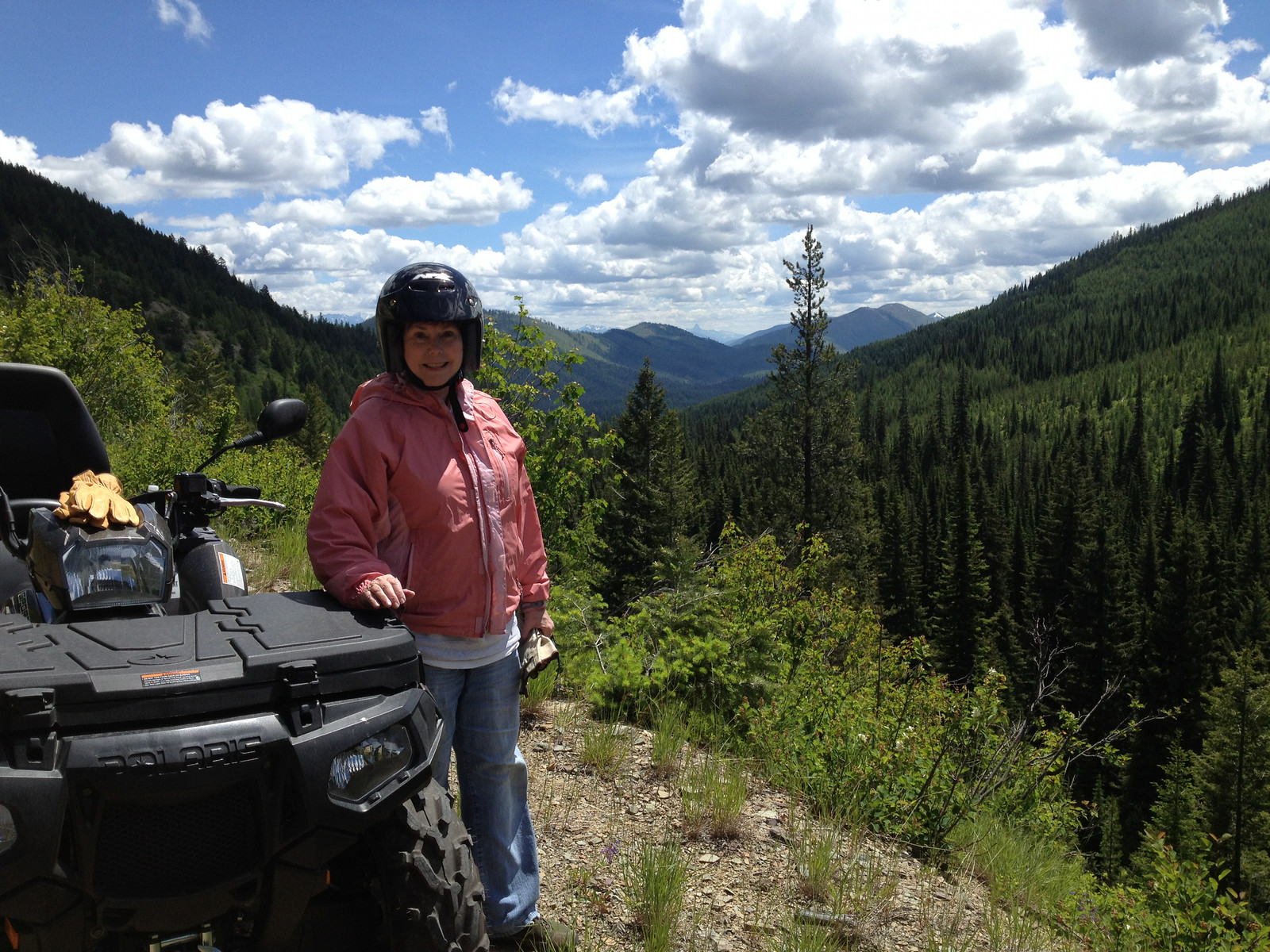 Boomer woman wearing a helmet stands next to an ATV with mountain scenery behind her.