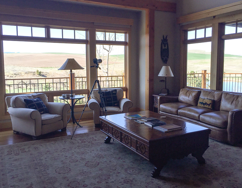 A brown leather sofa and two beige easy chairs surrounded a large coffee table in the Grey Cliffs Ranch great room.